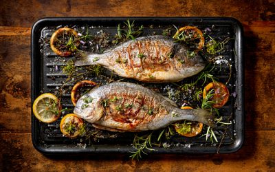 Grilled  fish, sea bream, dorada with the addition of spices, herbs and lemon on the grill plate located on a wooden background,  top view. Healthy eating concept